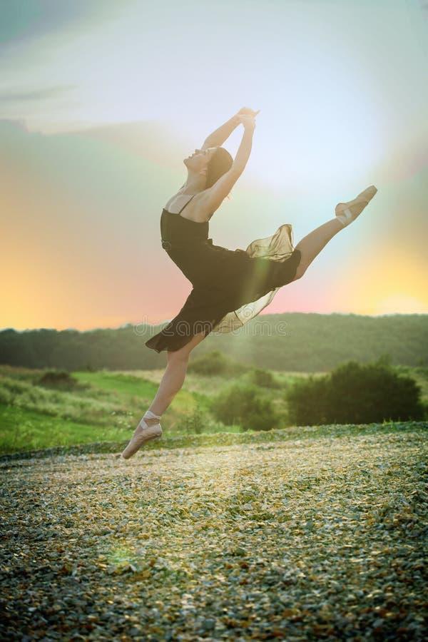 Balettflickadansaren hoppar på solnedgången royaltyfria bilder