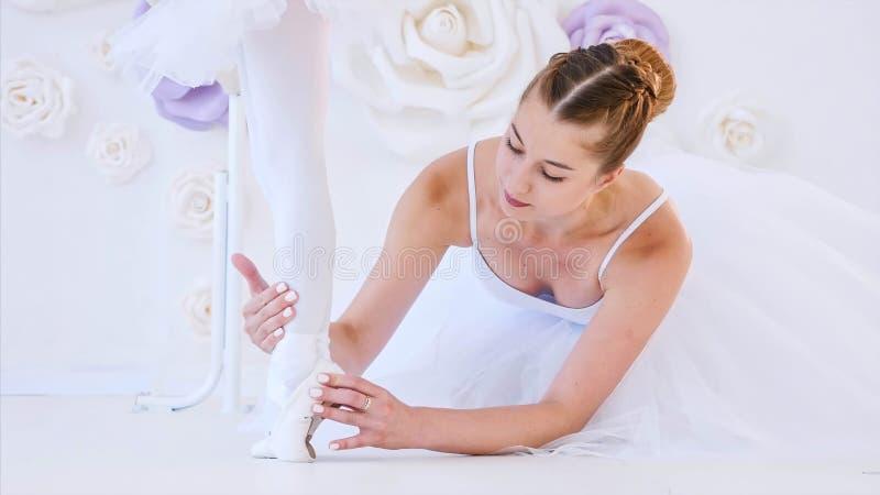 Balettläraren hjälper lilla flickan att sträcka fot som lyfter anseende på tåspetsarna arkivbild