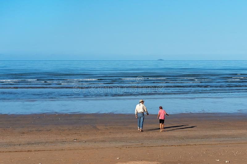 Grandfather And Grandson Walking On The Beach royalty free stock images