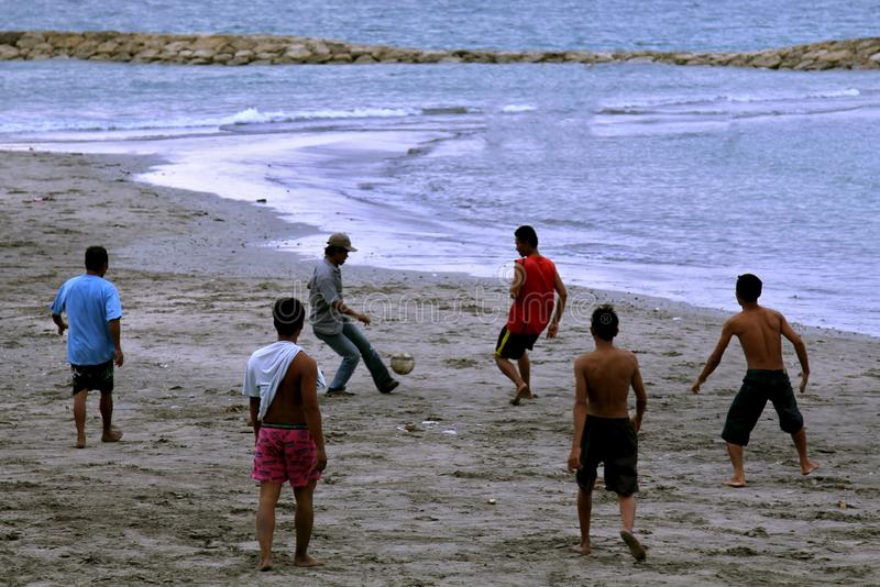 bali Gennaio 2019 Marinai locali e pescatori Gli uomini giocano a calcio su una spiaggia sporca sui precedenti dell'acqua immagine stock libera da diritti