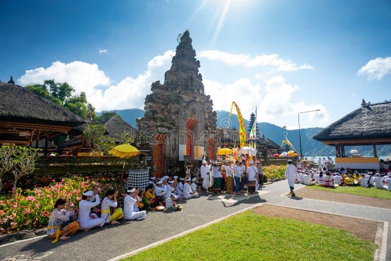 Bali, Indonésia - 27 de abril de 2019 - povos que rezam em um ritual no templo de Ulun Danu Beratan imagem de stock royalty free