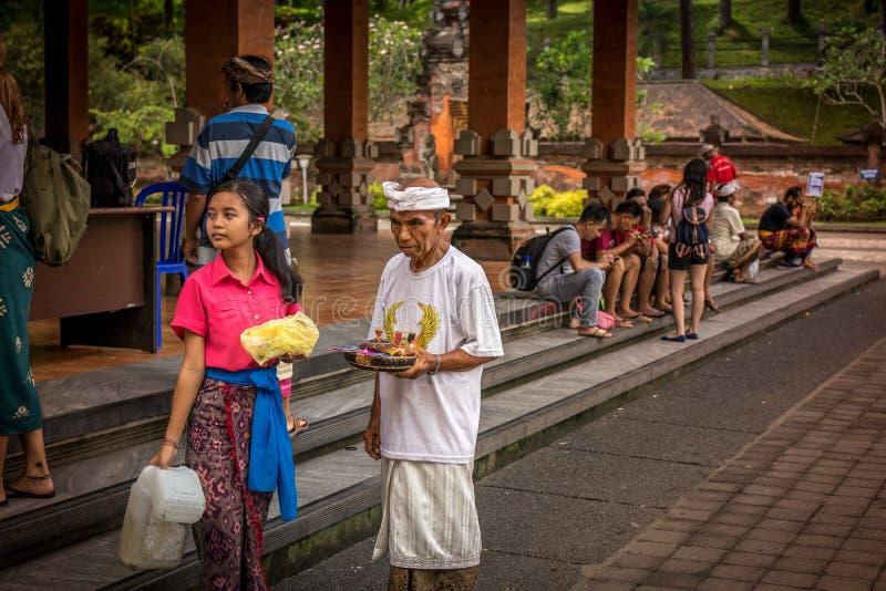 BALI, INDONÉSIA - 5 DE DEZEMBRO DE 2017: Moça do Balinese na roupa tradicional com o pai no templo de Tirta Empul fotos de stock royalty free