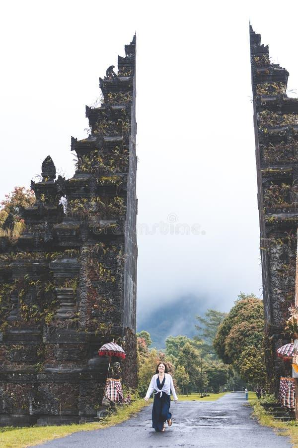 BALI, INDONÉSIA - 3 DE JANEIRO DE 2019: Mulher nova do turista em um fundo grande das portas do balinese Console de Bali, Indonés foto de stock