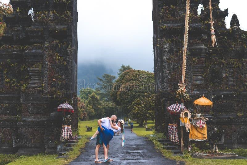 BALI, INDONÉSIA - 3 DE JANEIRO DE 2019: Pares novos da lua de mel em um fundo grande das portas do balinese Console de Bali, Indo foto de stock royalty free