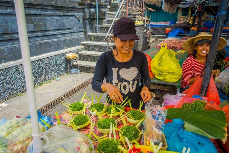 BALI, INDONÉSIA - 8 DE MARÇO DE 2017: A mulher não identificada faz um arranjo das flores dentro de uma caixa feita das folhas na imagem de stock