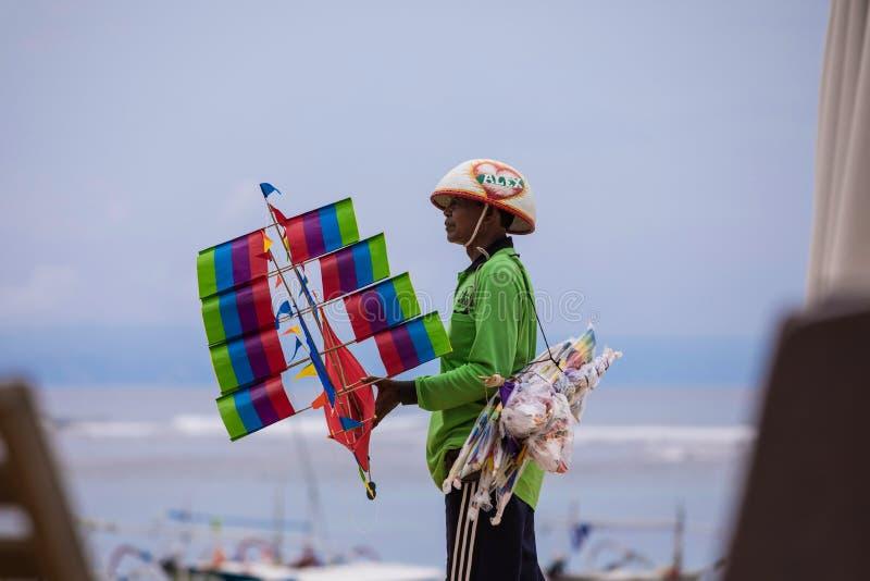 BALI, INDONÉSIA - 16 11 2017: O homem do Balinese vende papagaios feitos a mão na praia de Bali, Indonésia foto de stock