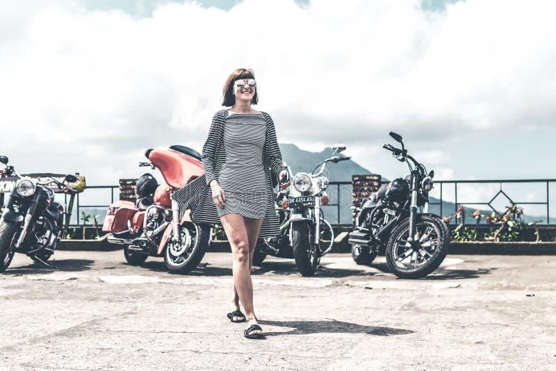 BALI, INDONÉSIE - 12 AOÛT 2018 : Femme sur le fond de motos de Harley Davidson, volcan de Batur photo libre de droits
