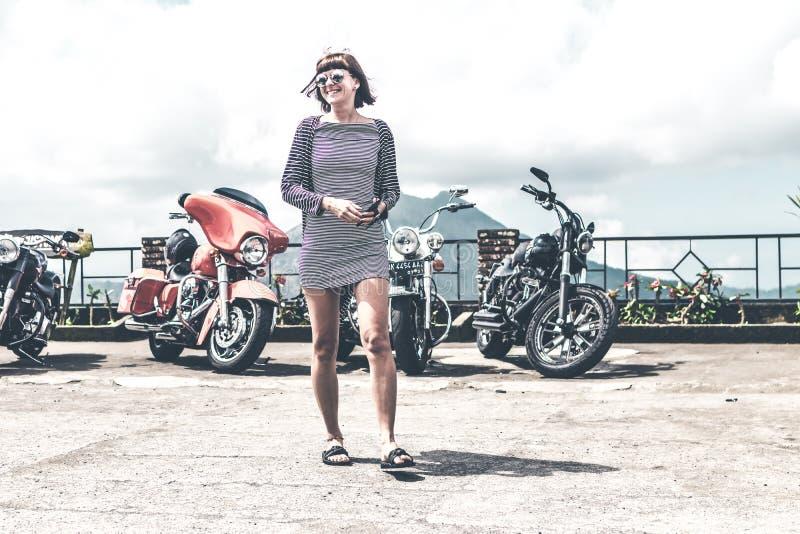 BALI, INDONÉSIE - 12 AOÛT 2018 : Femme sur le fond de motos de Harley Davidson, volcan de Batur photographie stock