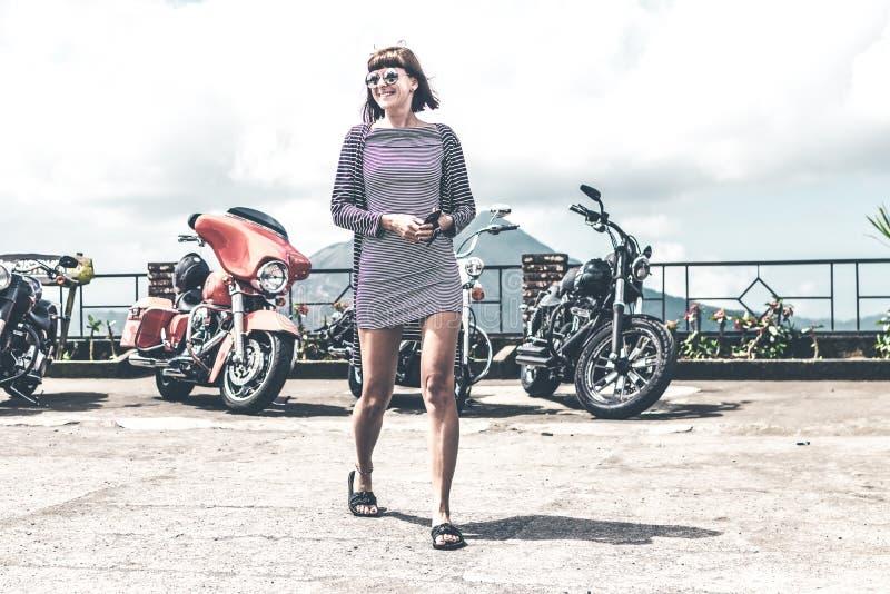 BALI, INDONÉSIE - 12 AOÛT 2018 : Femme sur le fond de motos de Harley Davidson, volcan de Batur image stock