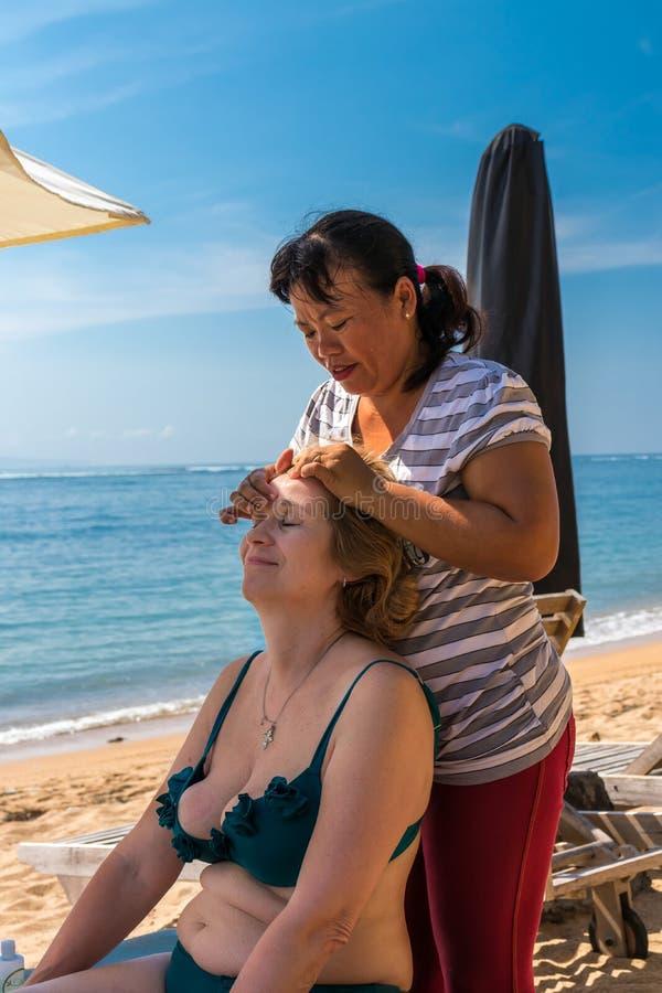 BALI, INDONÉSIE - 14 AVRIL 2017 : La femme supérieure obtient le massage principal sur la plage photographie stock