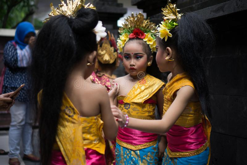 BALI/INDONESIA- 28-ОЕ ДЕКАБРЯ 2017: 3 молодых балийских танцора нося традиционные балийские одежды и составляют, подготавливали к стоковое изображение