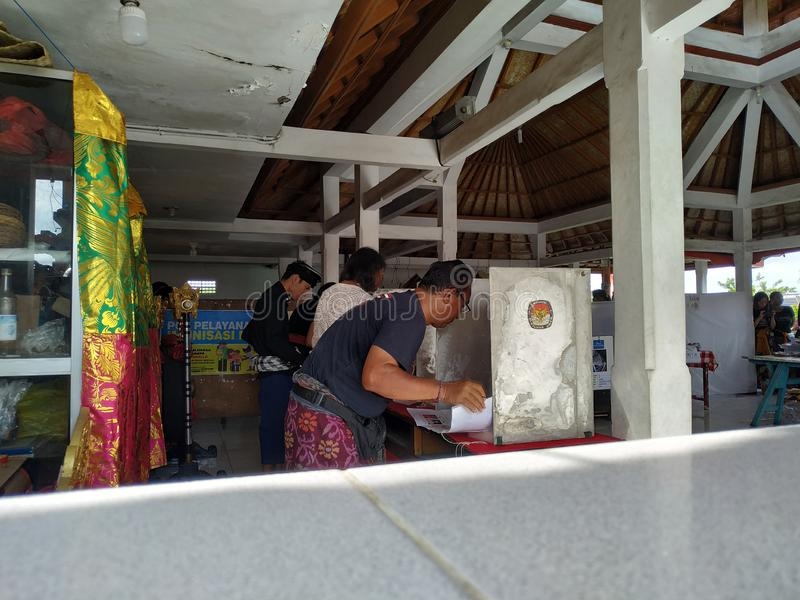 BALI/INDONESIA-APRIL 17 2019: Balijczyków ludzie głosują dla prezydenta 2019 parlamentu i Iść lokali/lów wyborczych używa obraz stock