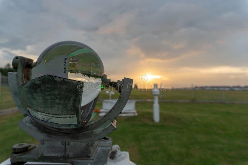 05 bali/indonesia-APRIL 2019: Campbell-stook bij Ngurah Rai-Meteorologiepost met groen gras en oranje zonsondergang op onder bewo stock fotografie