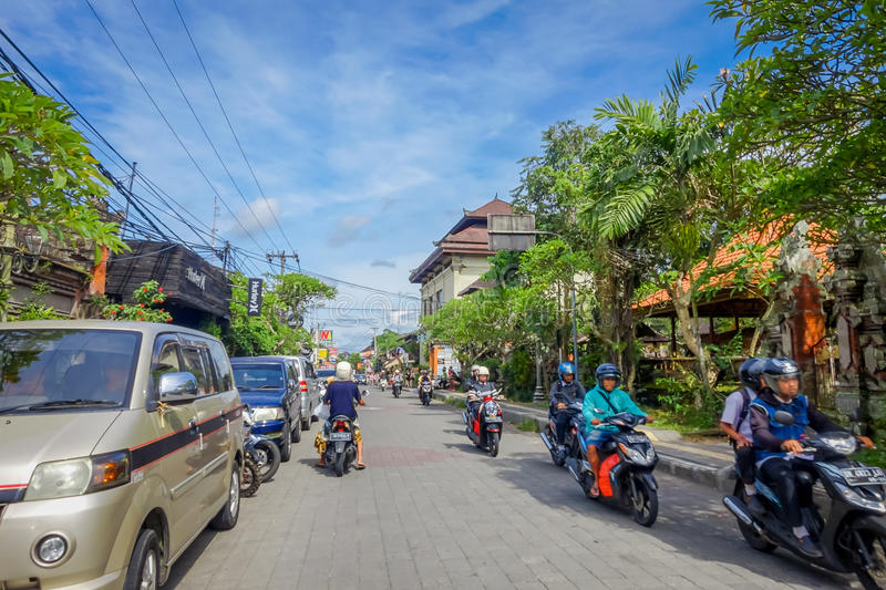 BALI, INDONESIA - APRIL 05, 2017: Motorcyclist going down the road in ubud, Bali royalty free stock photo