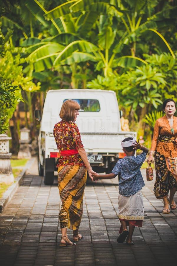 BALI, INDONESIA - 13 APRILE 2018: Bambino asiatico con la giovane donna europea sul giorno delle nozze di balinese Bambino indone immagini stock