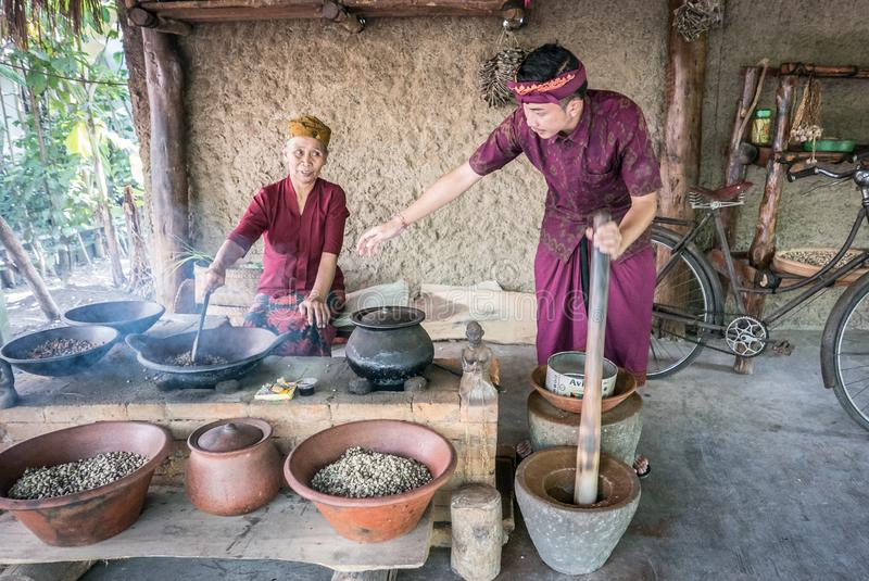 Old woman and young man roasting luwak coffee beans in Ubud stock photo