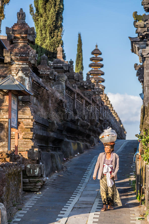 Bali, Indonesia - circa October 2015: Old lady carry offerings at Pura Ulun Danu Batur, Bali, Indonesia royalty free stock photography