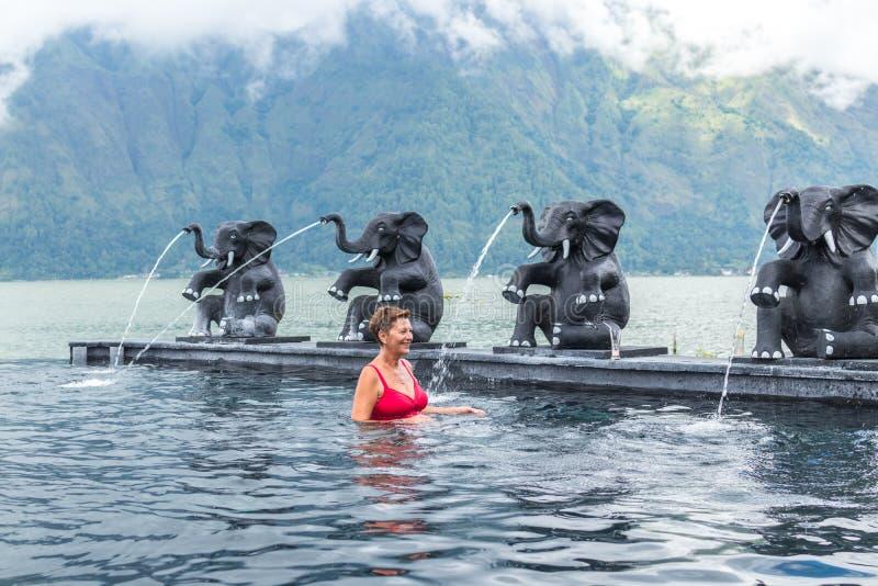 BALI, INDONESIA - 5 DE MAYO DE 2017: Natación mayor sana de la mujer en la piscina de la naturaleza Forma de vida activa Isla de  fotos de archivo