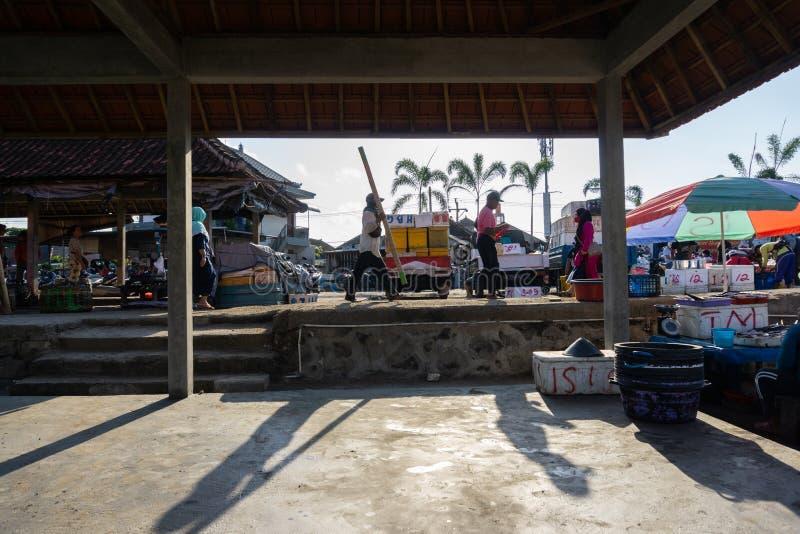 BALI/INDONESIA- 15 DE MAYO DE 2019: la atmósfera del mercado de pescados de Kedonganan-Bali Pescadores que pasan por para traer s fotos de archivo libres de regalías