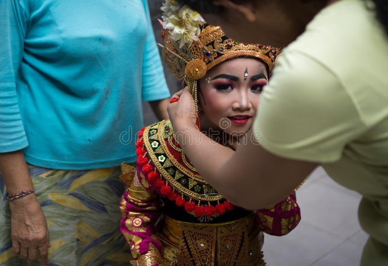 BALI/INDONESIA-DECEMBER 28 2018年:巴厘语舞蹈家,一名小妇女,在她的母亲帮助的头饰投入 一安慰 库存照片