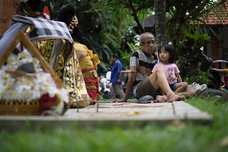 BALI/INDONESIA-DECEMBER 28 2017年:祖父照料他的孙女通过伴随他的观看艺术的孙女 免版税库存照片
