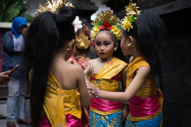 BALI/INDONESIA-DECEMBER 28 2017年:穿传统巴厘语衣裳的三位年轻巴厘语舞蹈家和组成,准备 库存图片