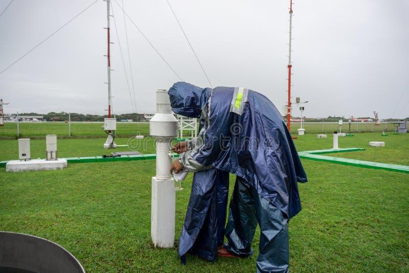 BALI/INDONESIA-DECEMBER 21 2017: Meteorologiczny obserwator sprawdza podeszczowego metr przy meteorologia ogródem mierzyć deszc zdjęcie royalty free