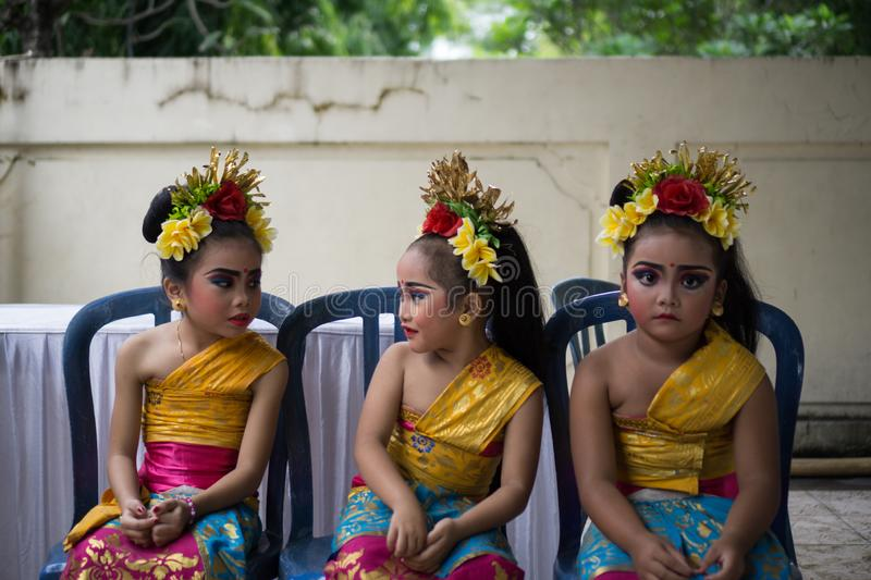 BALI/INDONESIA-DECEMBER 28 2017:Three young Balinese dancers wearing traditional Balinese clothes and make up, were preparing to stock photography