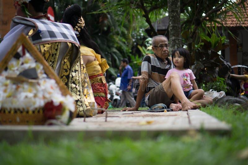 BALI/INDONESIA-, 28. DEZEMBER 2017: ein Großvater interessierte sich für seine Enkelin, indem er seine Enkelin begleitete, die ei lizenzfreies stockfoto