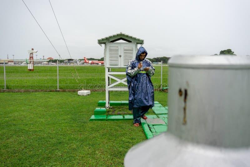 BALI/INDONESIA- 21 DICEMBRE 2017: Un osservatore meteorologico controlla la gabbia meteorologica al giardino della meteorologia p immagini stock