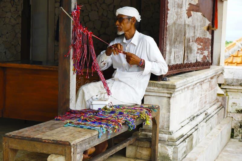 BALI, INDONESIA, gennaio 2018, un uomo anziano al tempio di Uluwatu che fa i braccialetti sacri fotografie stock libere da diritti