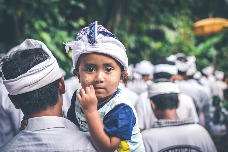 BALI, INDONESIA - JULY 4, 2018: Balinese children on a traditional ceremony. Baby with father. BALI, INDONESIA - JULY 4, 2018: Balinese children on a royalty free stock photos