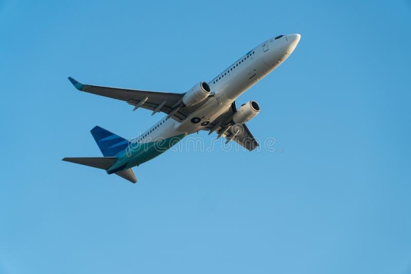 BALI/INDONESIA-JUNE 06 2019: Garuda Indonesia ett av flygbolagen i Indonesien, som sammanfogar himmellaget, flyger över blåtten arkivfoto