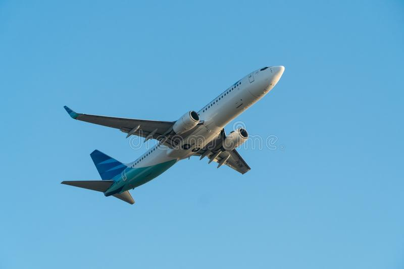 BALI/INDONESIA-JUNE 06 2019: Garuda Indonesia, one of the airlines in Indonesia which join the sky team, is flying over the blue. Sky. Landing gear is in the stock photos