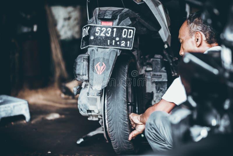 BALI, INDONESIA - 17 MAGGIO 2018: Sostituzione della gomma della motocicletta, installazione in garage Riparazione del motorino d fotografie stock
