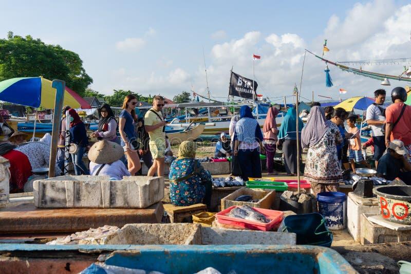 BALI/INDONESIA-, 15. MAI 2019: Die Atmosphäre des Kedonganan-Bali-Fischmarktes Ein Paar Touristen von Europa gehen genießen lizenzfreie stockbilder