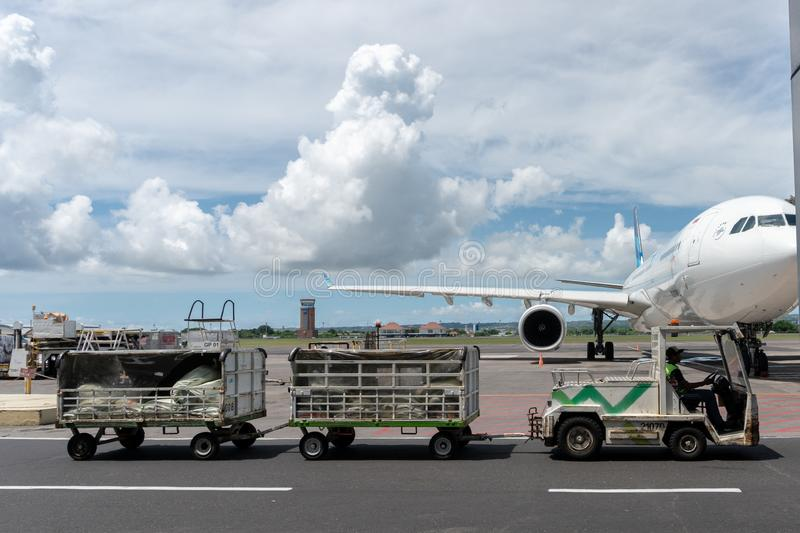 BALI/INDONESIA-MARCH 27 2019: Airport vehicles pulls passengers baggage to the arrival terminal when the sunny day with cumulus royalty free stock images