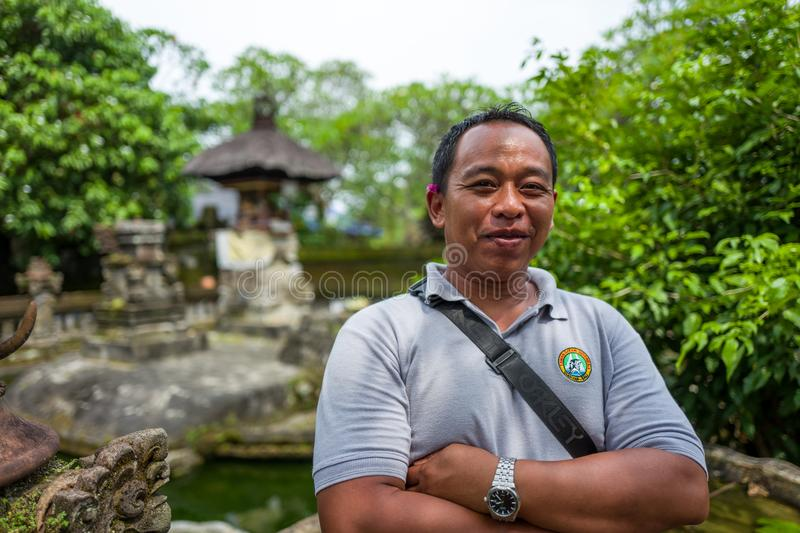 Bali, Indonesia - March 22, 2018: A Bali driver smiling at camera at Batuan temple. stock image