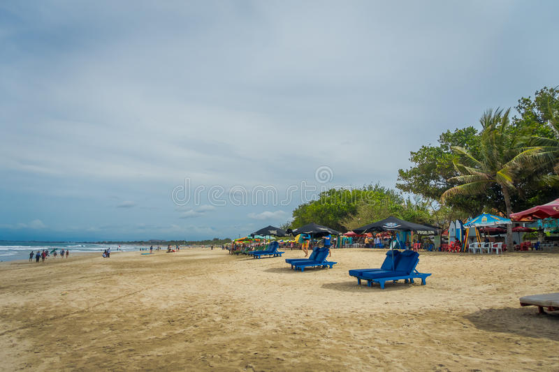 BALI- INDONESIA MARCH 08 2017: Late Afternoon at Low Tide tourists strolling on Legian Beach stock photo