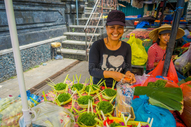 BALI, INDONESIA - MARCH 08, 2017: Unidentified woman do an arrangement of flowers inside of a box made of leafs in a royalty free stock photos