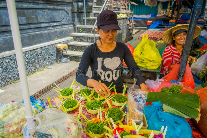 BALI, INDONESIA - MARCH 08, 2017: Unidentified woman do an arrangement of flowers inside of a box made of leafs in a stock image
