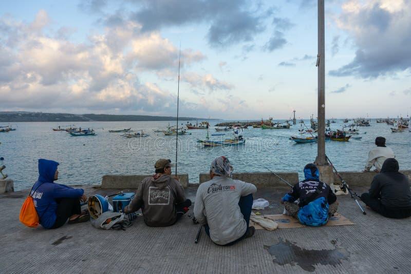 BALI/INDONESIA-MAY 15 2019年:在一晴朗和有一点阴天,某些人度过他们的与钓鱼的周末 E 免版税库存照片