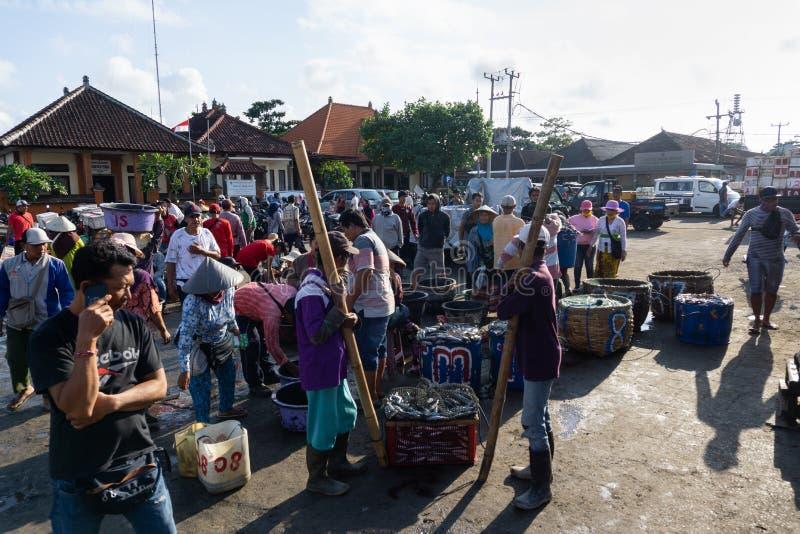 BALI/INDONESIA-MAY 15 2019年:完成卖他们的抓住的直接钓鱼的渔夫 他们排队由称 库存照片