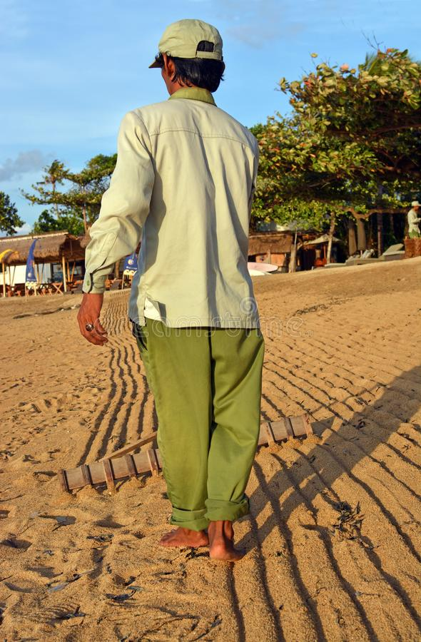 Balinese man grooms beach at Sanur, Bali in morning, Indonesia stock photo