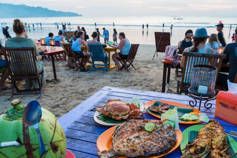 Sea food restaurants on Jimbaran beach in Bali, Indonesia. Bali, Indonesia - May 12, 2017: Jimbaran tropical beach is a main popular balinese attraction, famous royalty free stock photos