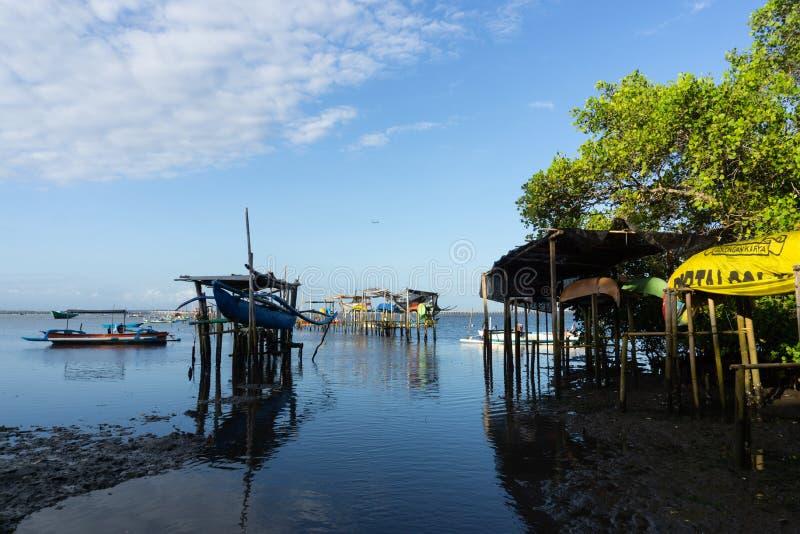 BALI/INDONESIA-MAY 10 2019: N?gra traditionella fartyg f?r Balinese som h?ngs p? bambu, n?r havsvattnet g?r tillbaka royaltyfri foto