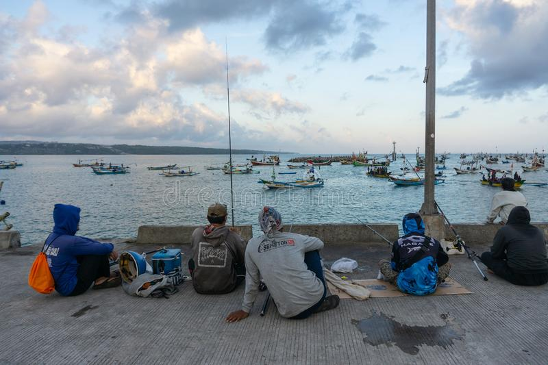 BALI/INDONESIA-MAY 15 2019: På en solig och litet molnig dag spenderar några personer deras helg med fiske De ?r royaltyfri fotografi