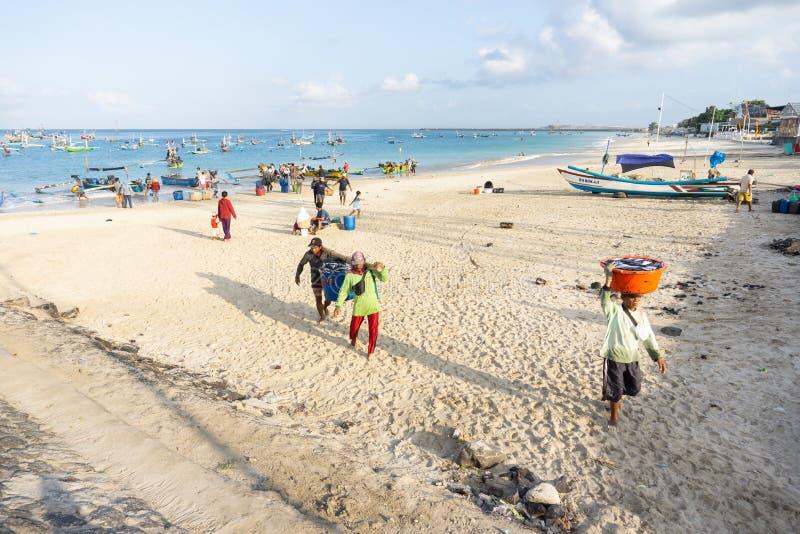 BALI/INDONESIA-MAY 15 2019: Rybacy iść do domu od morza, przynoszą ich chwyta rybi rynek sprzedawać bezpośrednio Kedonganan- obrazy stock