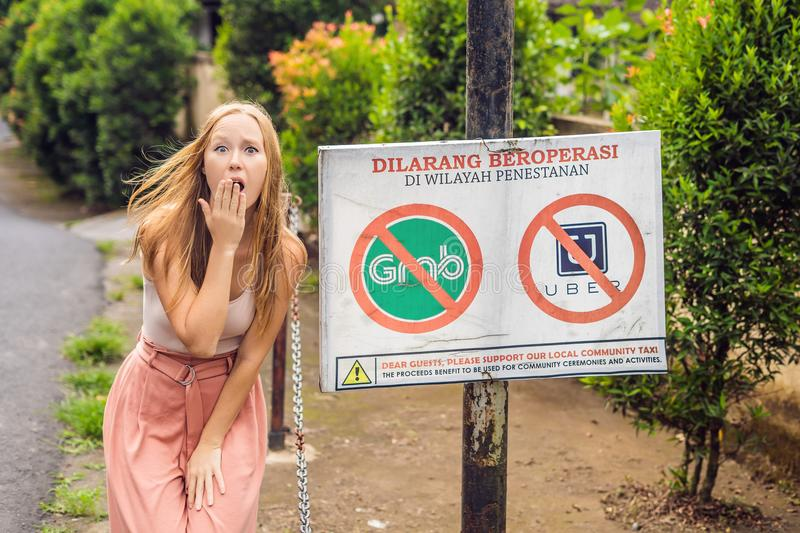 BALI, INDONESIA - 21 May, 2018: Young woman looks at protest sign on a wall in Indonesian objecting to Uber and Grab taxi drivers stock photos