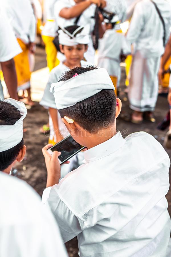 BALI, INDONESIA - OCTOBER 9, 2018: Balinese boys with smartphone on a traditional ceremony in Ubud. royalty free stock photography